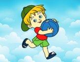 Criança que joga com esfera de praia